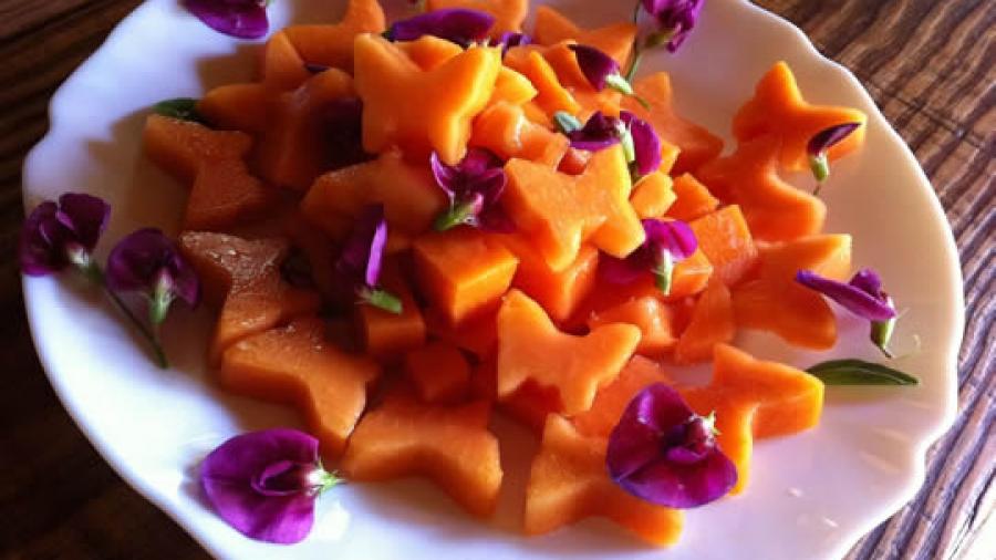 Papaya-Würfel und -Schmetterlinge mit Platterbsen