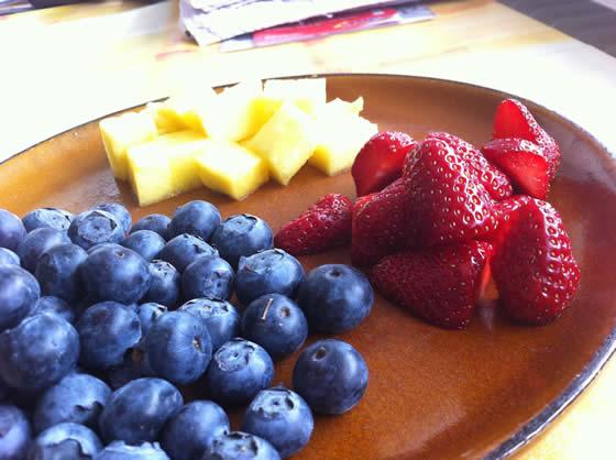 Buntes Frühstück für das Kind: Heidelbeeren, Ananas und Erdbeeren